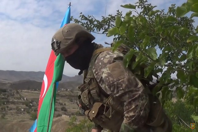 An Azeri serviceman plants an Azerbaijani flag somewhere in Jabrayil district in Azerbaijan on September 27, after the Azerbaijani Army took it under control. Photo by Azerbaijan Defense Ministry/EPA-EFE