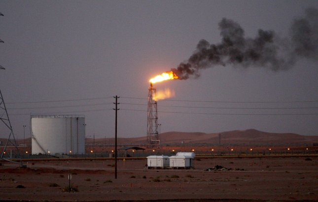 A gas flame behind pipelines in the desert at Khurais oil field, about 99 miles from Riyadh, Saudi Arabia, June 23, 2008. According to Saudi state-owned oil company Aramco, two of its oil facilities in Saudi Arabia, Khurais and Abqaiq, were set on fire Saturday. File Photo by Ali Haider/EPA-EFE