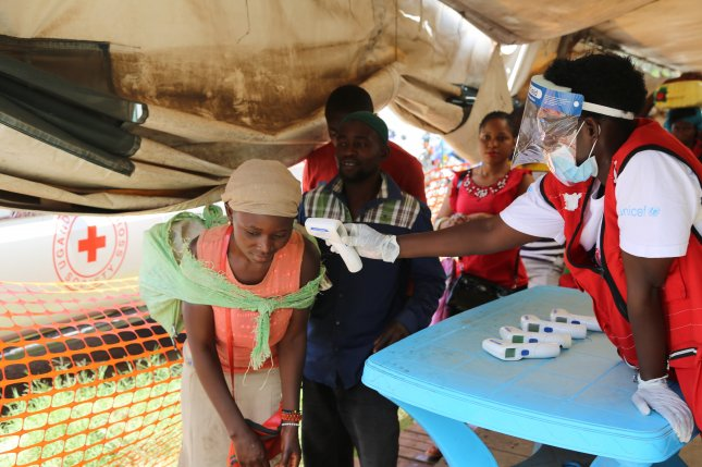 A World Health Organization worker checks patients' temperatures at Mpondwe border point with the Democratic Republic of Congo, near Bwera, Uganda. Photo by EPA-EFE