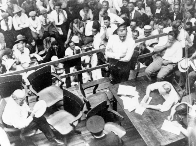 Photograph shows William Jennings Bryan (seated, left, with fan) and Clarence Darrow (standing, center, with arms folded) at an outdoor courtroom during the Scopes Trial (Tennessee v. Scopes) in Dayton, Tenn., in July 1925. UPI File Photo