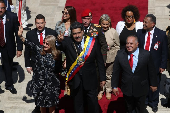 Venezuelan President Nicolas Maduro waves before a speech at the National Assembly Monday, accompanied by Venezuelan first lady Cilia Flores (L) and National Assembly President Diosdado Cabello. Photo by Miguel Gutierrez/EPA-EFE