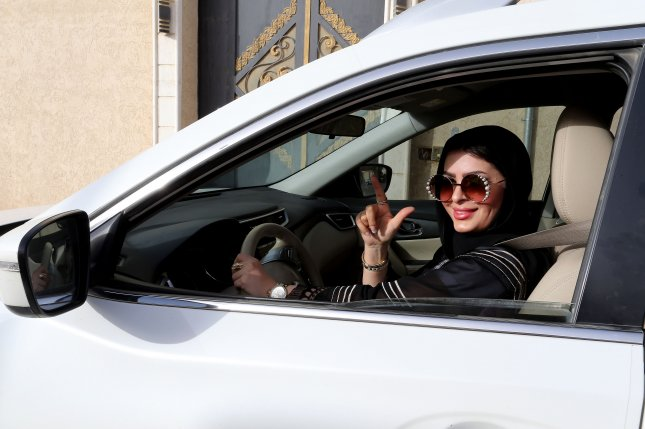Huda al-Badri, 30, poses behind a steering wheel early Sunday morning in Riyadh as women are allowed to drive for the first time in Saudi Arabia. Photo by Ahmed Yosri/EPA
