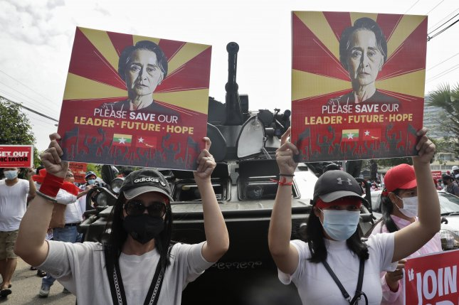 Demonstrators hold up placards calling for release of detained Myanmar State Counselor Aung San Suu Kyi in front of an armored vehicle during a protest this week outside the Central Bank in Yangon, Myanmar. Photo by Lynn Bo Bo/EPA-EFE