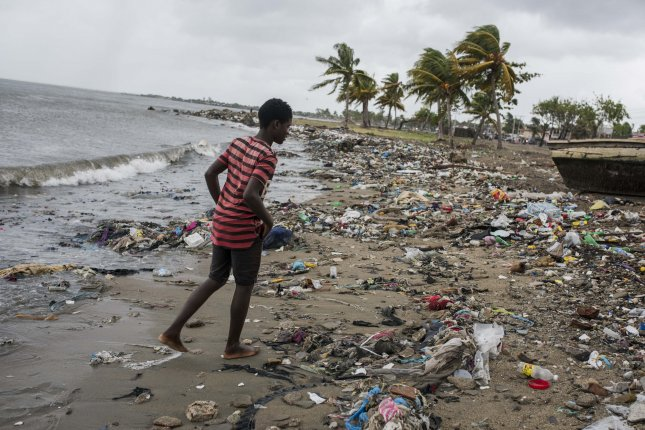A young man walks along the beach covered with debris carried by strong winds in Cap Haitian, Haiti, on Thursday. Photo by Jean Marc Herve Abelard/EPA