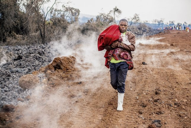 A Congolese man carries a baby as he evacuates the town of Goma in the aftermath of the eruption of Mount Nyiragongo volcano over Goma, Democratic Republic of the Congo on Wednesday. Photo by Michel Lunanga/EPA-EFE