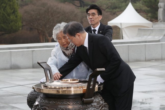 Yoon Cheong-ja (L), whose son died in the Cheonan sinking, approaches South Korean President Moon Jae-in as he prepares to burn incense at Daejeon National Cemetery on Friday. Photo by Yonhap/EPA-EFE
