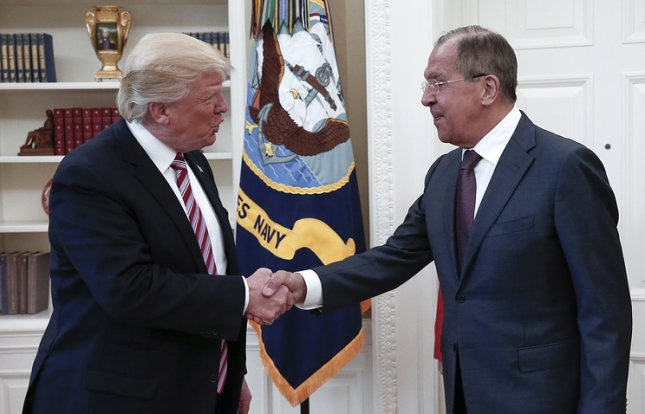 President Donald Trump and Russian Foreign Minister Sergei Lavrov (R) shake hands in the Oval Office of the White House on Wednesday. Photo by Alexander Shcherbak/TASS