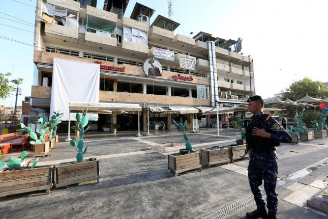 An Iraqi police officer mills at the site of bombing at Alfaqma ice cream shop in Karrada district, Baghdad, on Tuesday. The Islamic State claimed responsibility for the bombing. Photo by Ali Abbas/EPA