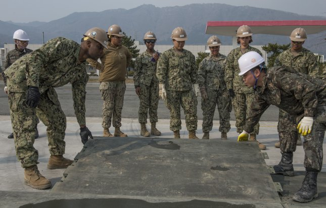 U.S. Navy Utilitiesman 3rd Class Brandon Matthews, from Charleston, S.C., assigned to Naval Mobile Construction Battalion 4, and his Republic of Korea Naval Mobile Construction Battalion counterpart install a ramp plate on an expeditionary airfield during an airfield damage repair exercise at Jinhae, Korea, on Monday as part of exercise Foal Eagle 2016. Foal Eagle is an annual, bilateral training exercise designed to enhance the readiness of U.S. and ROK forces, and their ability to work together during a crisis. Photo by Mass Communication Specialist 1st Class Charles E. White/U.S. Navy
