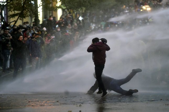 Lebanese riot police spray water cannons to disperse anti-government protestors during a protest outside of the Lebanese Parliament in downtown Beirut Saturday. Photo by Wael Hamzeh/EPA-EFE