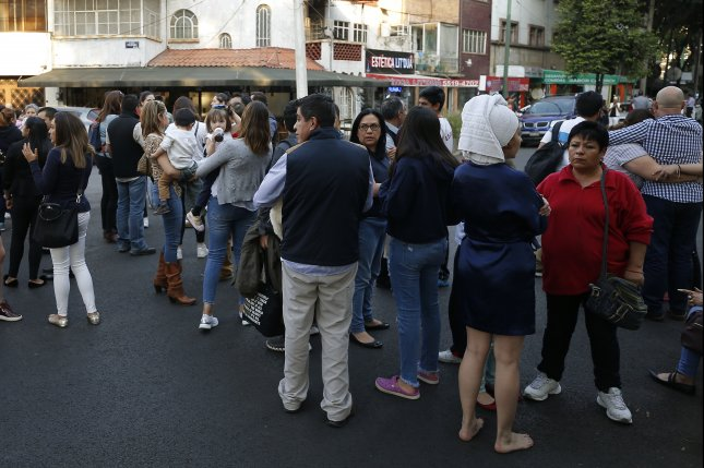 People wait outside their offices and vehicles in Mexico City after an earthquake Friday. A military helicopter surveying damage crashed while landing Friday night, killing 13 people on the aircraft or on the ground, Mexican officials said. Photo by Jose Mendez/EPA