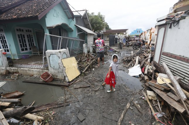 Residents walk among debris Tuesday in a devastated area after a tsunami hit Sunda Strait in Sumur, Banten, Indonesia. Photo by Adi Weda/EPA-EFE