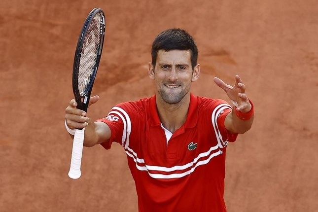 Novak Djokovic of Serbia celebrates after beating Stefanos Tsitsipas of Greece in the men's singles final at the 2021 French Open tennis tournament Sunday at Roland Garros in Paris. Photo by Ian Langsdon/EPA-EFE/