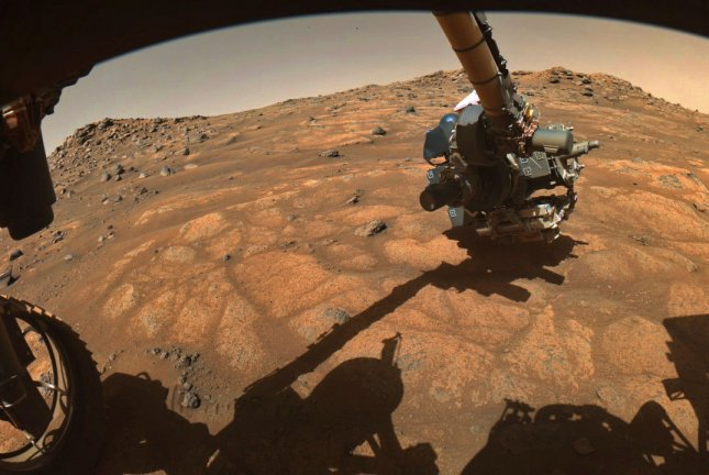 The Mars rover Perseverance extends a robotic arm in preparation to drill a rock sample on Mars. Photo courtesy of NASA