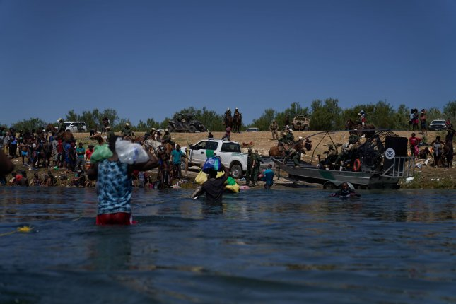Migrants cross the Rio Grande river from Ciudad Acuna, Mexico, on September 20. A coalition of advocacy groups is calling for the Biden administration to reverse a policy that's expedited the expulsion of migrants from Haiti. File Photo by Allison Dinner/EPA-EFE