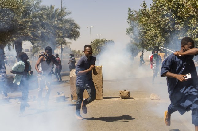Demonstrators run from police tear gas in Khartoum, Sudan, during a protest to oppose President Omar al-Bashir. Guterres said the African nation needs sanctions relief to make necessary reforms. File Photo by EPA EFE