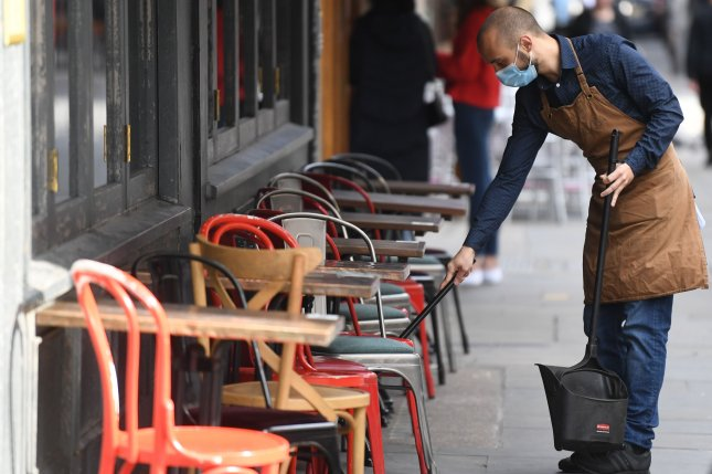 A worker in a face mask cleans a cafe in London on Thursday. The British government announced new lockdown measures in the northeastern part of the country. Photo by Neil Hall/EPA-EFE