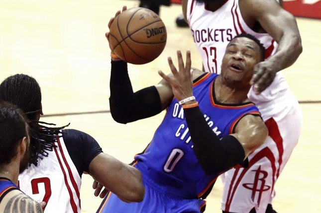 Oklahoma City Thunder guard Russell Westbrook (C) is fouled by Houston Rockets guard James Harden (R) while going to the basket in the first half of Game 2 of the NBA Western Conference playoffs on April 19 at the Toyota Center in Houston, Texas. File photo by Larry W. Smith/EPA
