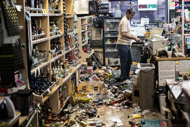 An employee stands behind the counter amid fallen bottles that smashed on the ground after an earthquake at a gas station and liquor store in Ridgecrest, California, was hit by a 7.1-magnitude earthquake Friday night. Photo by Etienne Laurent/EPA