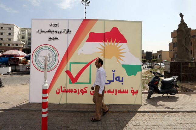 A man walks next to a poster for a referendum vote for independence at the old city of Erbil, Kurdistan region in northern Iraq, on September 24. Photo by Mohamed Messara/EPA-EFE