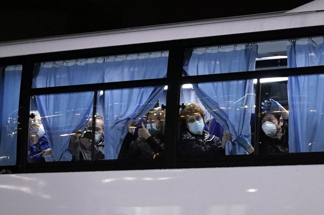 U.S. citizens wave from a bus as they leave the Diamond Princess cruise ship docked at Daikoku Pier Cruise Terminal for repatriation in Yokohama, south of Tokyo early Monday. Photo by Franck Robichon/EPA-EFE