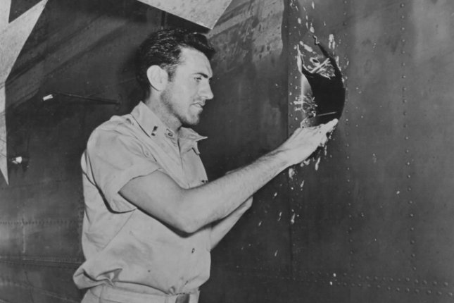 First Lt. Louis Zamperini peers through a hole in his B-24D Liberator Super Man made by a 20mm shell over Nauru on April 18, 1943. File Photo courtesy of the National Archives and Records Administration