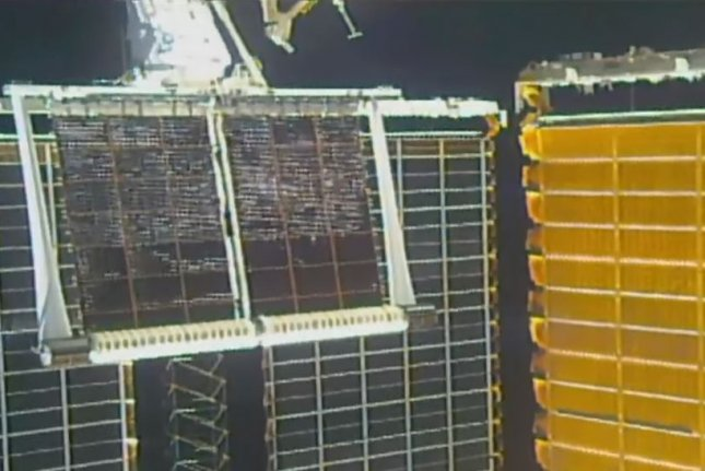 A new solar array unrolls outside the International Space Station on Friday during an astronaut spacewalk. Photo courtesy of NASA