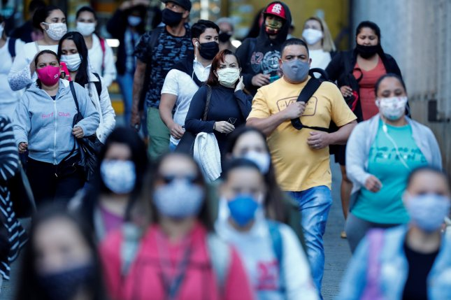People with face masks walk in a street amid coronavirus pandemic in Sao Paulo, Brazil on June 19. This week Brazil's government announced that it has signed a $127 million deal to begin producing an experimental COVID-19 vaccine. Photo by Sebastio Moreira/EPA-EFE