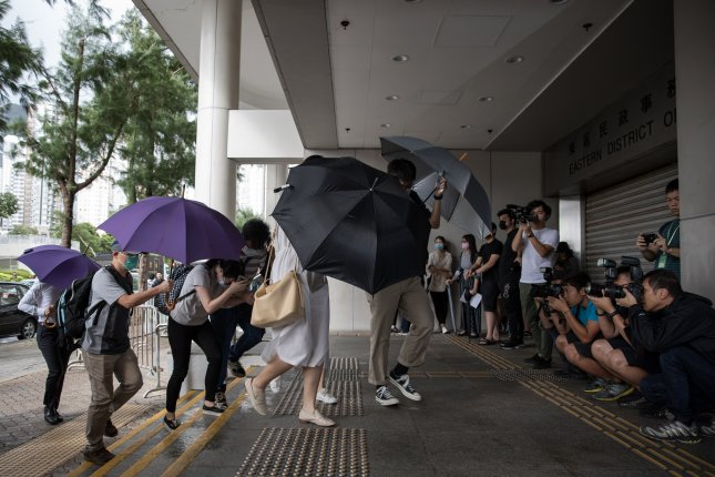 Anti-extradition protesters protect themselves from the rain with umbrellas as they arrive at the Eastern Magistrates' Court in Hong Kong, China, on Wednesday. Photo by Jerome Favre/EPA-EFE