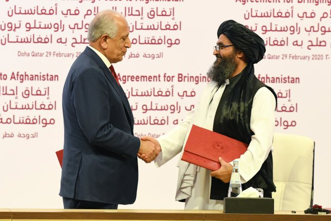 U.S. Special Representative for Afghanistan Reconciliation Zalmay Khalilzad (L) and Taliban co-founder Mullah Abdul Ghani Baradar shake hands during the signing ceremony of the U.S.-Taliban peace agreement in Doha, Qatar, on Saturday. Photo by Stringer/EPA-EFE