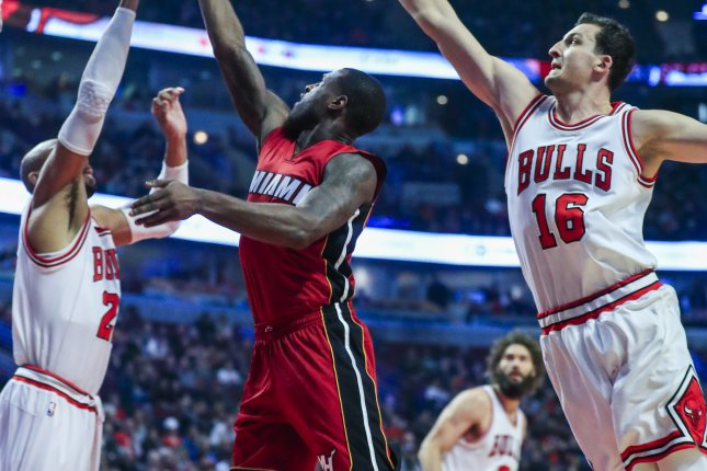 Miami Heat guard Dion Waiters (C) shoots between Chicago Bulls forwards Taj Gibson (L) and Paul Zipser (R) in the first half on Jan. 27, 2017 at the United Center in Chicago. (EPA/TANNEN MAURY)