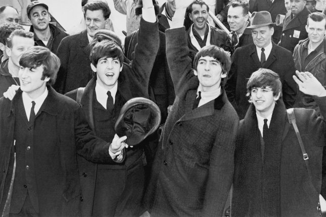 The Beatles wave to the thousands of screaming teenagers after their arrival at Kennedy Airport in New York in February 1964. Beatles documentary series Get Back is coming to Disney+ over three days in November. File Photo by United Press International