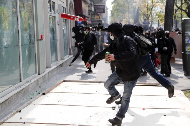 A Black Blocs protester throws a projectile towards the glass windows of a bank during a demonstration of the French trade unions members and the Yellow Vest movement marking May Day in Paris on Wednesday. Photo by Ian Langsdon/EPA-EFE