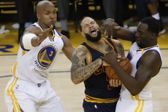 Golden State Warriors players Dreymond Green (R) and David West (L) block a shot against Cleveland Cavaliers guard Deron Williams (C) in the first half of Game 1 of the NBA Finals on June 1 at Oracle Arena in Oakland, Calif. Photo by John G. Mabanglo/EPA