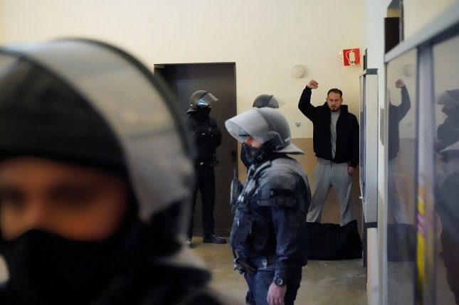 Spanish rapper Pablo Duro, known professionally as Pablo Hasel, raises a fist on Tuesday as he is arrested by police at Lleida University in Catalonia, where he took refuge in the building after refusing to report to prison. Photo by Paul de la Calle/EPA-EFE