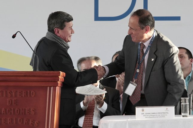 Colombia's chief peace negotiator Juan Camilo Restrepo, right, and the chief negotiator of the National Liberation Army, or ELN, rebel group, Pablo Beltran, left, shake hands during the start of peace talks between the Colombian government and the ELN in Quito, Ecuador, on Tuesday. Photo by Jose Jacome/EPA