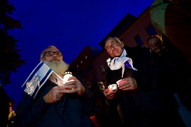 A man holds a candle and an Israeli flag during a vigil outside a synagogue in Halle an der Saale, Germany, on Friday. Photo by Filip Singer/EPA-EFE