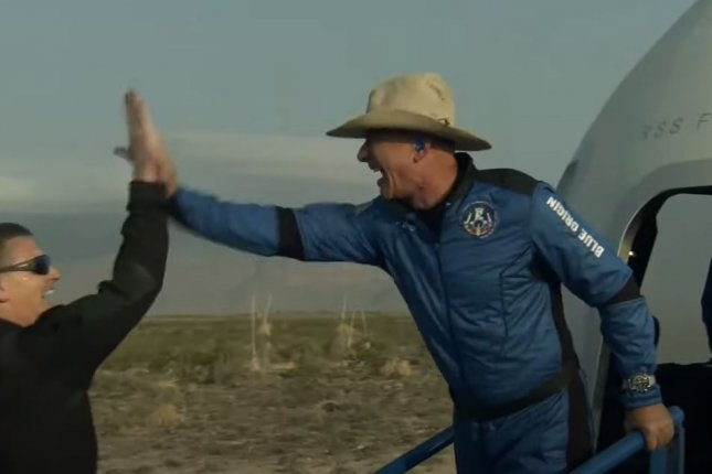 Jeff Bezos greets a Blue Origin crew member upon exiting the New Shepard capsule after the historic first crewed flight of the vehicle from Texas on Tuesday. Photo courtesy of Blue Origin