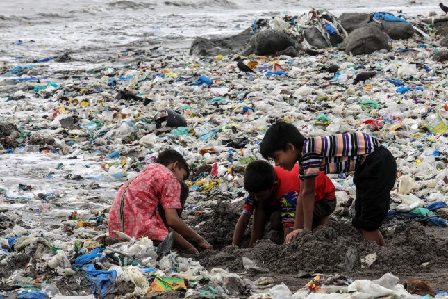 Children play amid a dumping ground for plastic waste near the Arabian Sea coast in Mumbai, India. File Photo by Divyakant Solanki/EPA-EFE