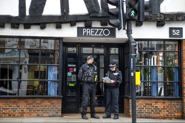 Police officers cordon off the Prezzo restaurant in Salisbury, Britain, Monday after a couple were sickened there. Officials said Monday the pair were not poisoned with the nerve agent used against former spy Sergei Skripal in March. Photo by Tolga Akmen/EPA-EFE