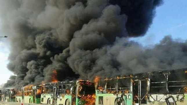 A handout photograph made available on Monday by the official Syrian Arab News Agency it said shows flames and smoke rising from green government buses, used to evacuate people from areas besieged by rebels, after they were set ablaze, in Idlib province, Syria on Sunday. Photo by SANA/European Pressphoto Agency