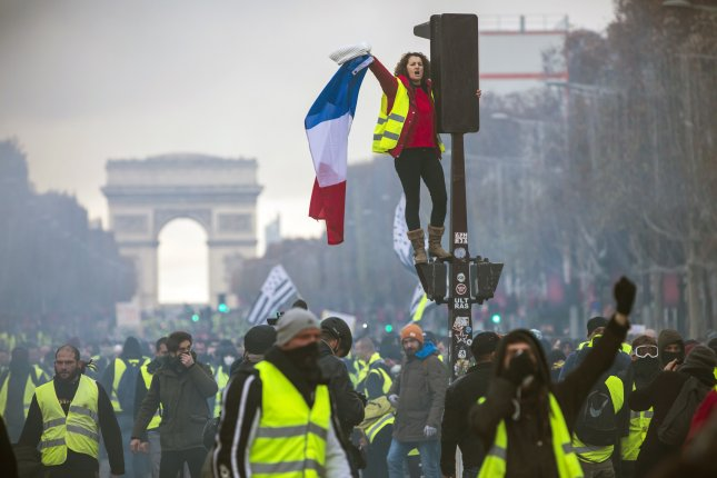 A woman wearing a yellow vest, as a symbol of protest against higher fuel prices, waves a French flag during clashes with police on Paris' Champs Elysee in November. File Photo by Christophe Petit Tesson/EPA-EFE