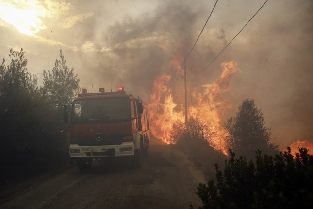 More than 20 people died as three forest fires spread throughout in Greece on Monday, damaging homes and vehicles, and prompting evacuations. Photo by Alexandros Vlachos/EPA