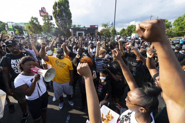 Protesters rally June 14, 2020, in the street near a Wendy's restaurant where Rayshard Brooks died days earlier inan Atlanta Police Department officer-involved shooting. File Photo by John Amis/EPA-EFE