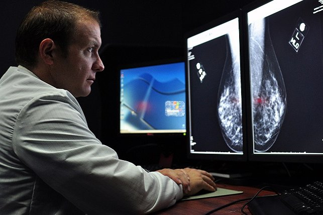 Lt. Cmdr. Erik Ramey, from Van Nuys, Calif., stationed at U.S. Naval Hospital Yokosuka's radiology department, reviews a patient's X-ray as part of a routine screening mammogram. Photo by Tim Jensen/U.S. Navy