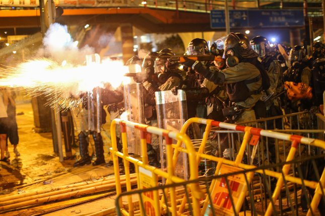 Riot police fire tear gas to disperse protesters taking part in a rally against police brutality in Hong Kong last month. China hasn't ruled out military intervention if the Hong Kong protests continue. File Photo by Jerome Favre/EPA-EFE