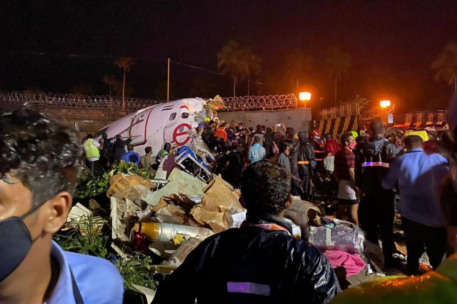 Officials inspect the wreckage site of an Air India plane crash at Calicut airport in Kozhikode, India, on Friday. Photo courtesy of India's Civil Defense/EPA-EFE