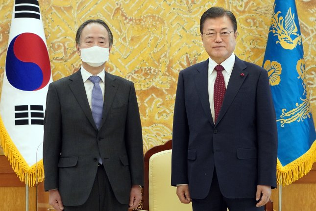 South Korean President Moon Jae-in (R) poses with Japanese Ambassador to South Korea Koji Tomita at the presidential Blue House in Seoul on Thursday. Photo by Cheong Wa Dae/EPA-EFE
