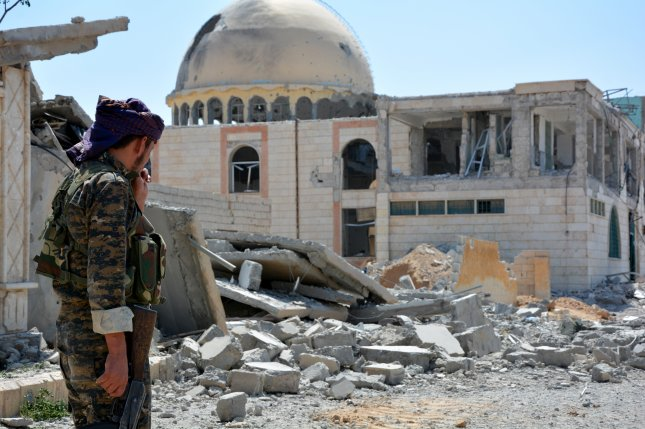 Soldiers patrol next to destroyed buildings at Raqqa city, Syria, on June 11. Photo by Youssef Rabie Youssef/EPA