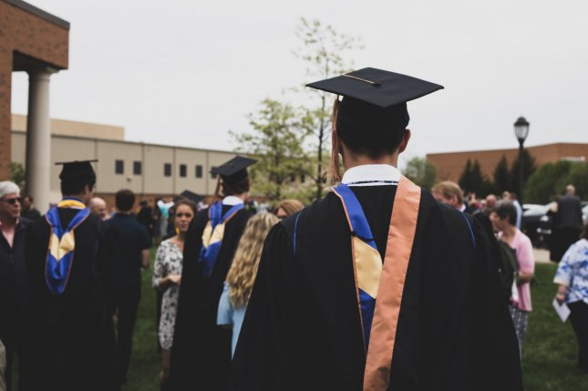 A graduate walks among his peers. Amazon announced that it will fully cover the cost of tuition for its employees' educations. Photo by Charles Deloye/UNSPLASH